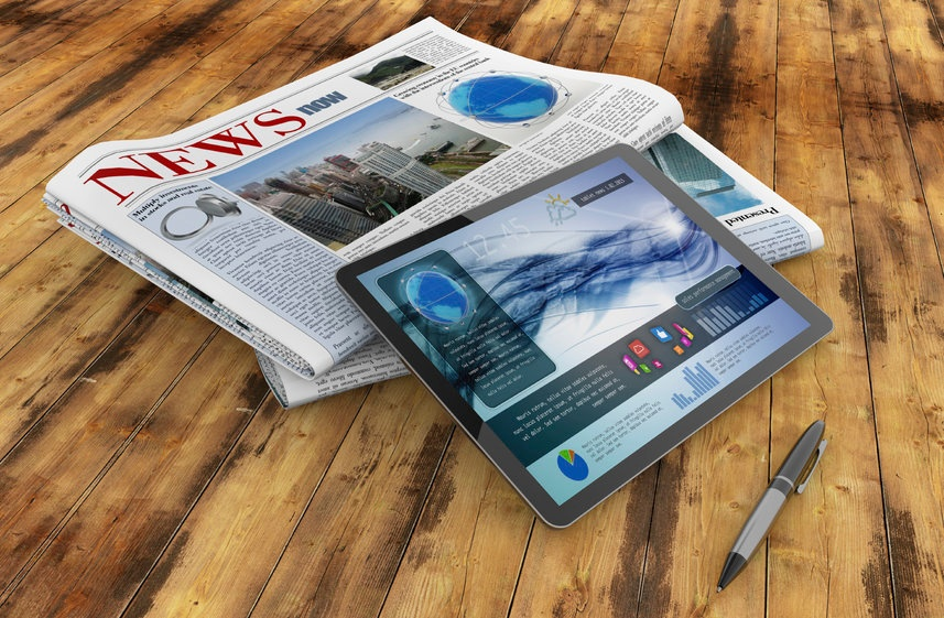 daily newspaper, tablet and pen on wooden desk